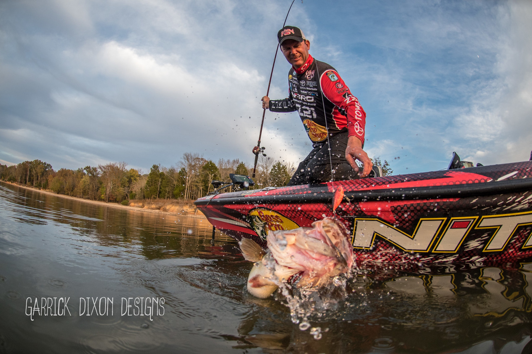 Wide action shot of Kevin VanDam about to pull a lively catch out of the water.